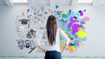 Young woman in concrete interior looking at wall with abstract sketch